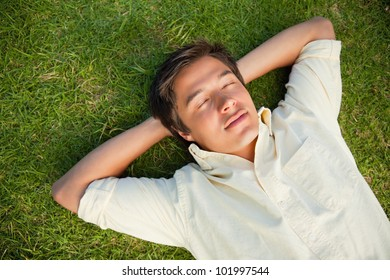Man lying on the grass with his eyes closed and both hands resting behind his neck