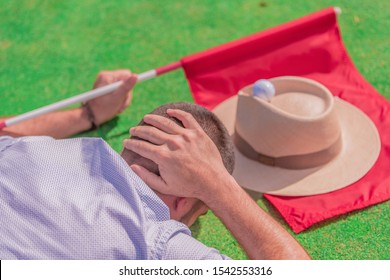 A man lying on a green field, with his hand on his head, next to a red flag, a hat and a golf ball on top. Concept of a day of relaxation and leisure.