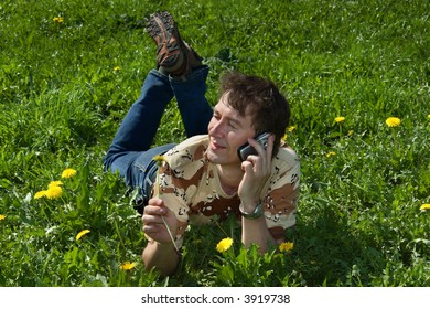 Man  lying on green grass and talking by phone.