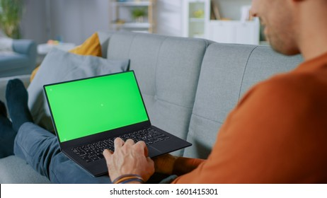 Man Lying on His Sofa At Home, Uses Laptop with Green Mock-up Screen. Over The Shoulder Shot of Anonymous Man in the Living Room.