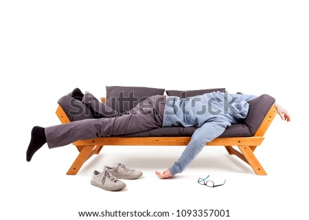 Man lying on sofa with headache or hangover isolated on white background.