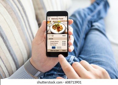 man lying on sofa and holding phone with app delivery food screen