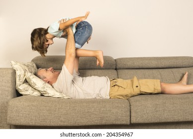 man lying on sofa and lifting up his daughter