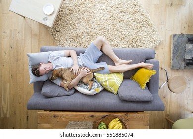 Man is lying on the sofa in the living room of his home. He has his dog lying on him who is also asleep.