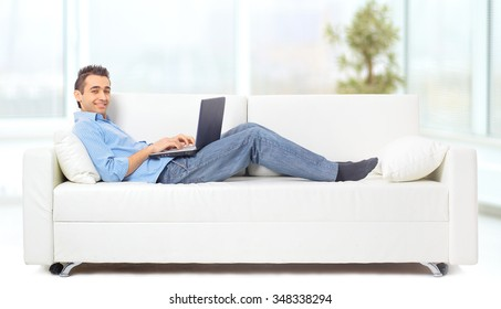 a man lying on the sofa working on the computer