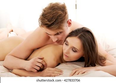 Man lying on woman in bedroom.