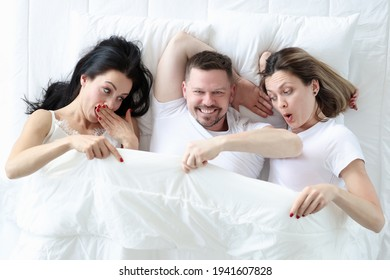 Man lying with two lovers in bed. Women looking under cover and wondering