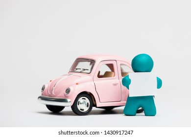 A man made from blue plasticine holding a blank sheet of paper next to a pink car on white background.