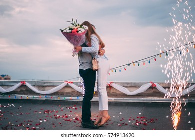 The man made a proposal to marry the girl. 				A man holding his beloved girl. On the duck buildings. Romance on the roof. Sparks cold fountains and flowers