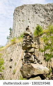 Man made stone tower outdoor, with unique basalt rock formation wall background.