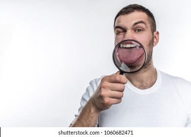 Man with magnifying glass is looking straight ahead and showing his tongue through the glass. Isolated on white background.