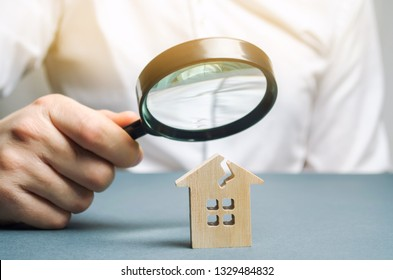 A man with a magnifying glass looks at a house with a crack. Damage assessment home and insurance risks. Estimation of the cost of repair and renovation of old buildings, property value.