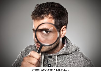 Man with magnifying lens over grey background. / Portrait of a normal man looking camera.