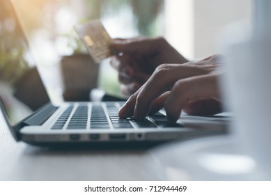 Man make an online shopping and internet banking on laptop computer by credit card payment, online banking, e commerce, e business, omnichannel or multichannel concept