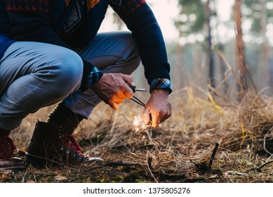 A man makes a fire with a flint