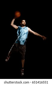 Man makes a hook shot. Skilled basketball player jumps high to throw a ball, isolated on black.