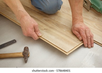 Man makes laying laminated panels, simulating light oak