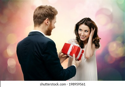 Man makes present to his lovely sweetheart on abstract and fantasy background
