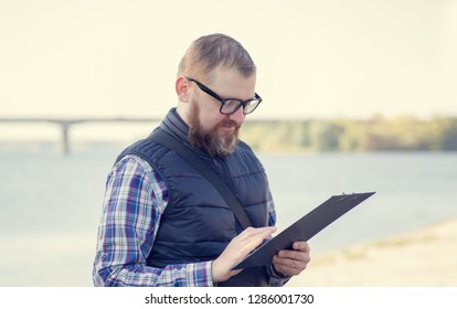 A man makes records about the state of water near the reservoir. Ecologist. Male middle age with a beard and glasses.