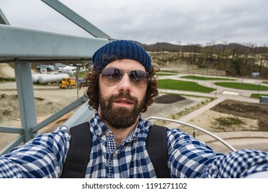 man makes selfies. Vlogging concept. Hipster, tourist with tousled hair and long beard looking at camera, taking selfie photo