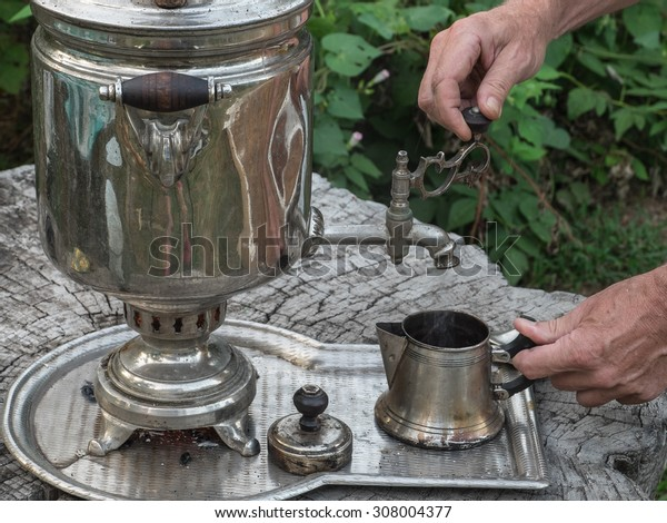 Man makes tea with water from boiling old samovar.