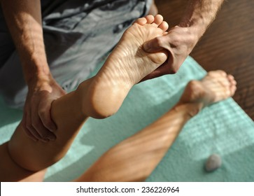 man makes woman massage feet and legs