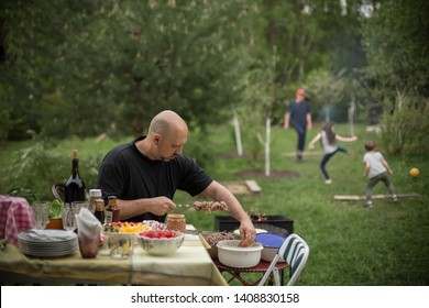 A man is making barbecue in dacha garden in Russia while kids are playing with ball in the background. Image with selective focus and toning