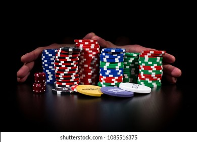 "Man is making a bet ""all in"". Male hands are placing stacks of poker chips forward over the black background. No face. Game addiction"