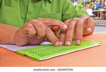 A man making Braille font on white paper