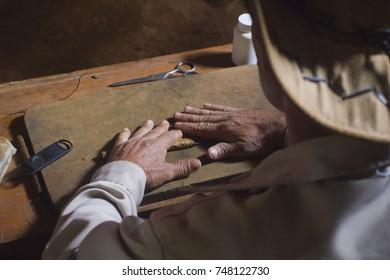 A man making a cigar with his hands in a plantation of Viñales, Pinar del Rio, Cuba