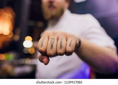 Man making clenched fist camera. Selective focus the cook has a tattoo on his fingers. cutlery patterns
