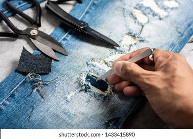 The man making ditressed jeans. DIY ripped jeans with scissors and razor.