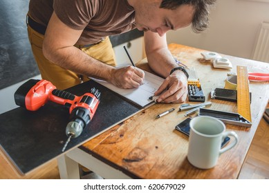 Man making draft plan using pencil on the table with tools