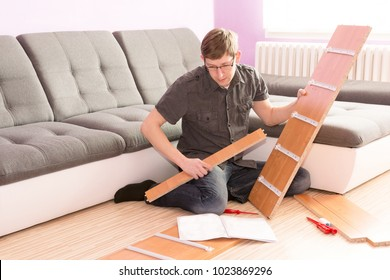 Man making furniture in the living room. Desperate man can not build a commode. Young man assembling furniture. Handy man.