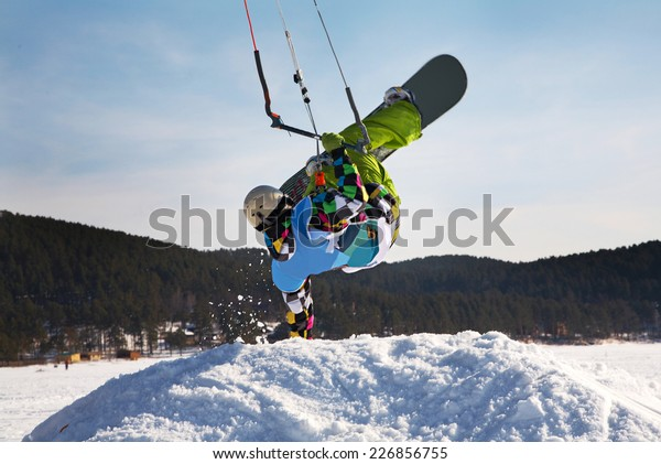 Man making hand stand on snowdrift winter snowkiting on a frozen lake