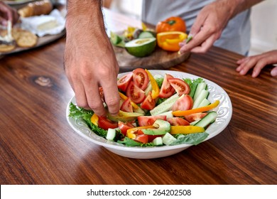 man making healthy fresh salad in kitchen