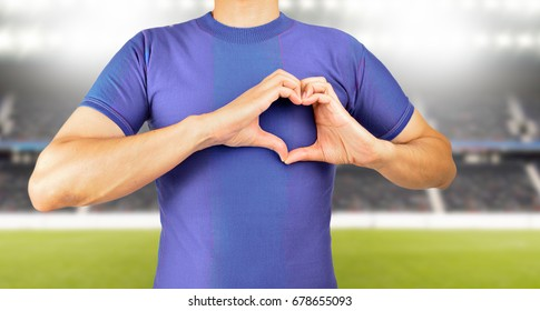 man making the heart shape with his hands over his chest in concept of love for football and soccer team at stadium in background.Concept of love to a team or colors in sport.