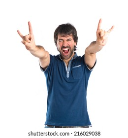 Man making horn gesture over white background