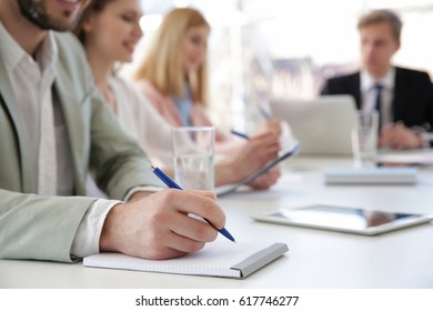 Man making notes in notebook at business presentation