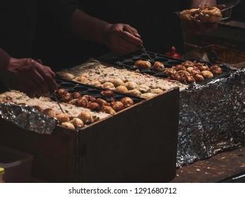 Man making octopus dumplings or takoyaki ,Japanese street food stall