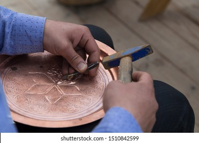 the man making pattern on the copper plate.