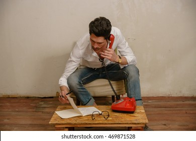 A man is making a phone call and looking in the notebook at his table