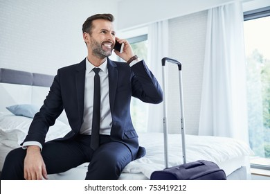 Man making phonecall while sitting in hotel room on business trip