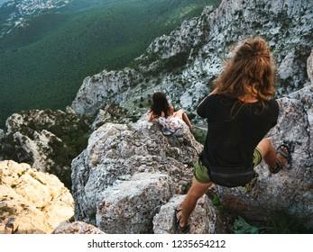 The man is making a photo of girl on the mountain peak. Ai-Petri mountain, Crimea