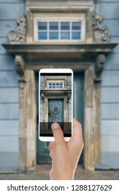 A man is making a photo of old blue door with beautiful columns, a visor and a window. Old town, Riga, Latvia on a mobile phone