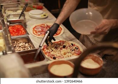 Man making pizzas at table, closeup view