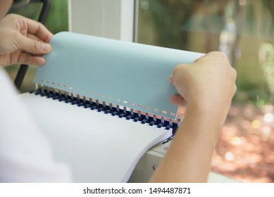 Man making report using comb binding machine - people working with stationary tools concept