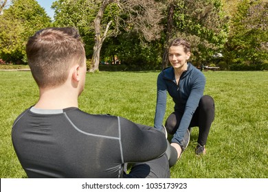 Man making sit-ups at the park with fitness training coach