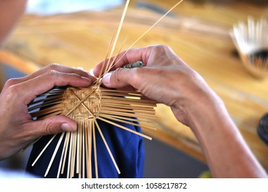 A man is making a small bamboo basket another popular handicraft product