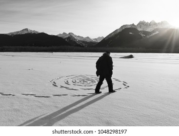Man making a sprial in the snow as the sun sets on the frozen Chilkat river near Haines, Alaska.